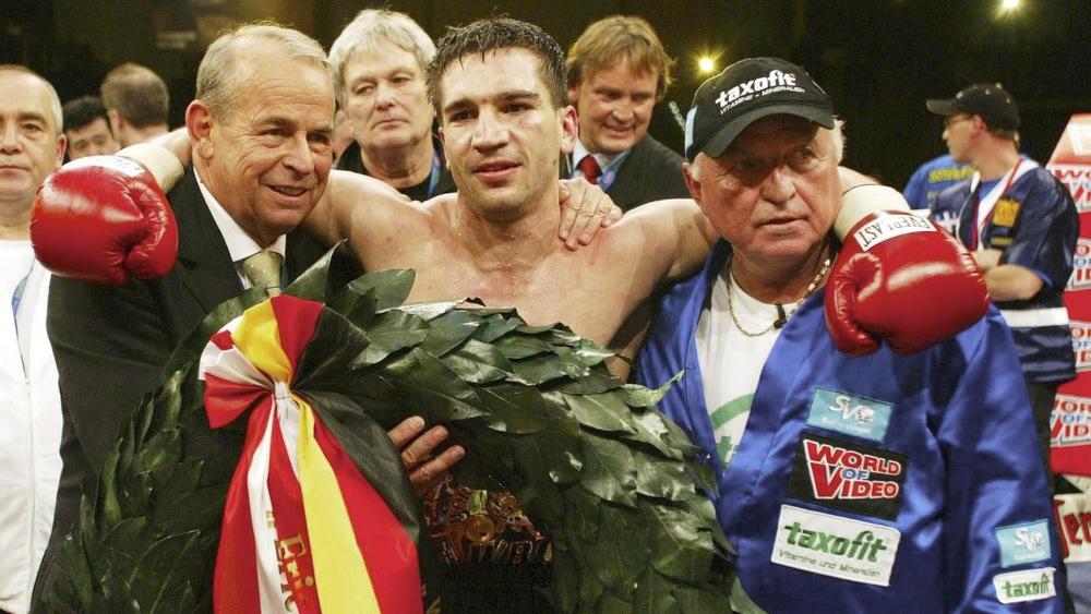 Le promoteur Wifried Sauerland (à gauche) et l'entraîneur Ulrich Wegner (à droite) entourent Markus Beyer après sa victoire le 5 avril 2003.
