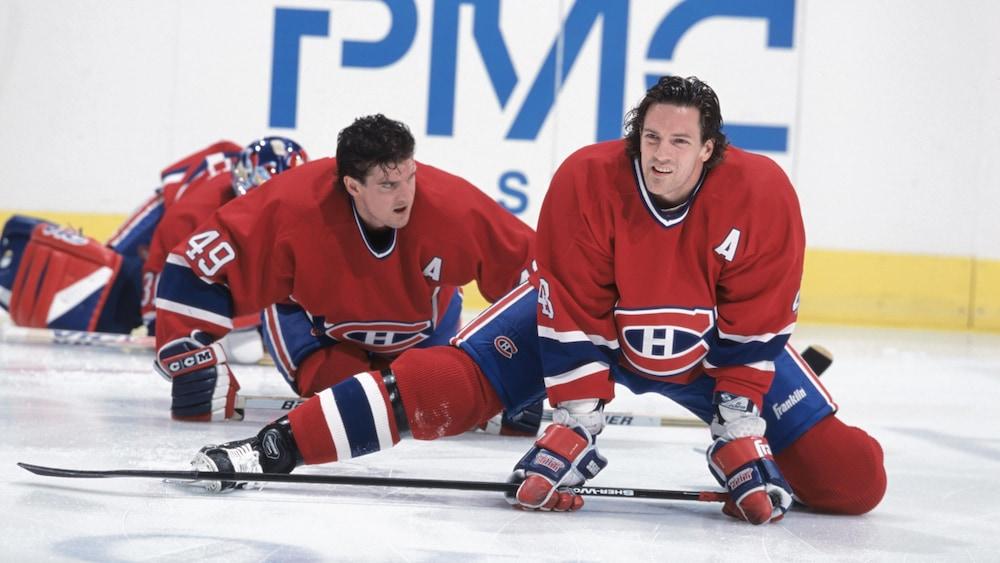 Patrice Brisebois (droite) et Brian Savage font des étirements avant un match du Canadien de Montréal, en 2002.