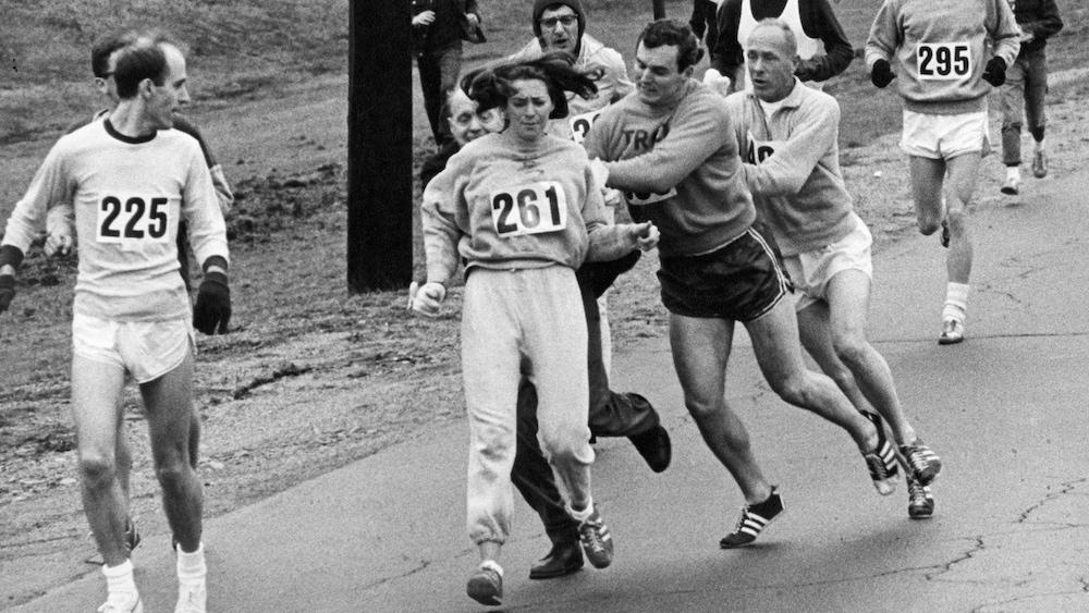 Tom Miller repousse Jock Semple (en noir) qui tente d'arracher son dossard à Kathrine Switzer lors du marathon de Boston en 1967.