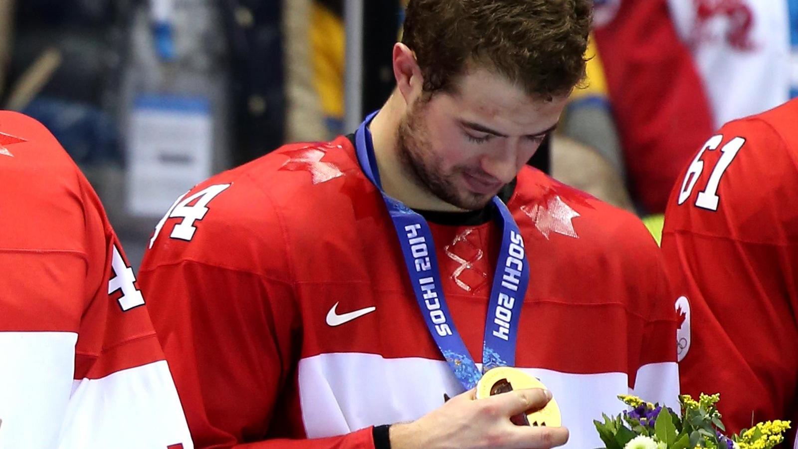 Le défenseur Marc-Édouard Vlasic regarde sa médaille d'or après la victoire du Canada en finale du tournoi de hockey masculin aux Jeux olympiques de Sotchi.