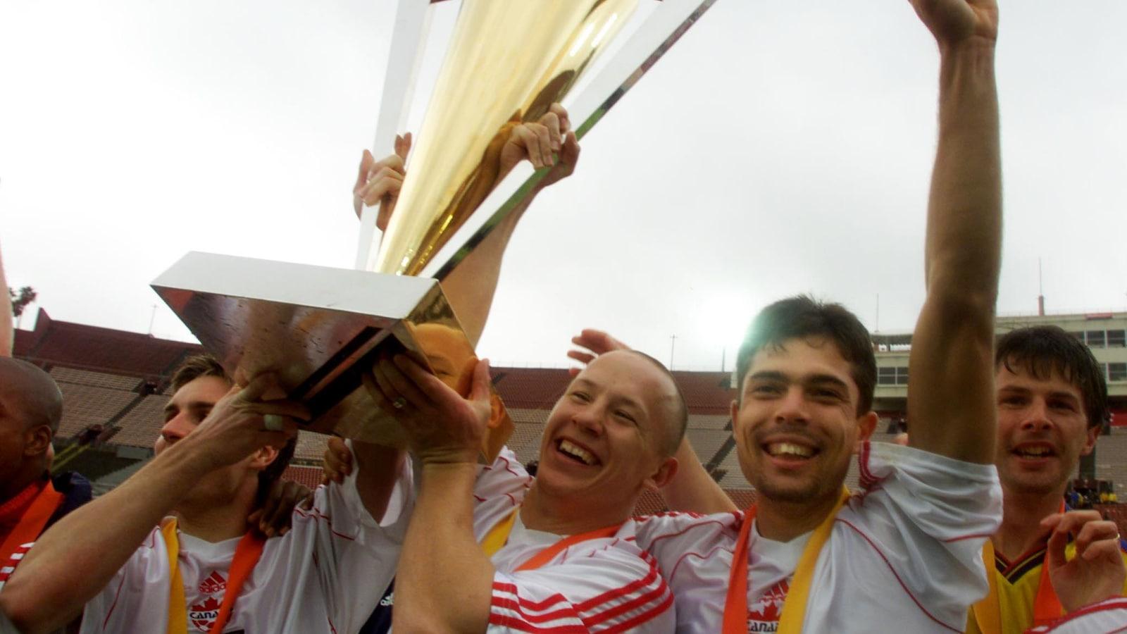Jim Brennan, Garret Kusch et Paul Fenwick, du Canada, soulèvent le trophée après avoir vaincu la Colombie en finale du tournoi de la Gold Cup en 2000.