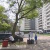 Des résidents devant un immeuble d'appartement avec des valises.
