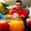Des urnes de verre contenant des aguas frescas mexicaines rouges et vertes.