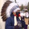 Le chef Billy Morin, portant une coiffe de plumes, s'adresse à la foule rassemblée sur le trottoir en parlant dans un mégaphone.