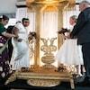 Deux femmes en robe de mariée, bouquet en main, montent sur une plateforme décorée en compagnie de leurs parents.