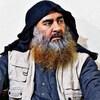 Abou Bakr al-Baghdadi, assis, porte un capuchon, une veste, une chemise et une barbe à deux couleurs (blanche et blonde).