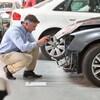 Un homme examine une voiture accidentée.