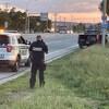 Un policier, au téléphone, hors de son véhicule se dirige vers un camion rangé sur le bas-côté.