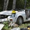 Une petite voiture est gravement endommagée. La voiture est collée contre plusieurs arbres, eux aussi endommagés.