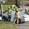Une dizaine de pompiers interviennent sur une voiture accidentée, à une intersection.