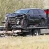 Un Dodge Durango noir ayant subi d'importants dégâts est remorqué par un camion rouge.