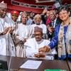 Muhammadu Buhari assis, une plume à la main, entouré de dizaines de représentants africains.