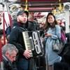 Photo d'un jeune homme qui joue de l'accordéon dans  une rame de métro bondée.