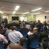 Une salle avec de nombreuses personnes assises sur des chaises, face à un groupe de personnes qui préside la rencontre.