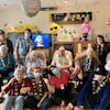 Des employés et des personnes âgées dans une salle commune portent des colliers fleuris de style hawaïen.