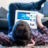 Un adolescent regarde une tablette, allongé sur le plancher du salon.