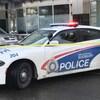 Une voiture de police et un policier derrière le périmètre de sécurité.
