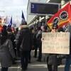Des gens manifestent devant l'aéroport de Montréal, une femme brandissant une pancarte sur laquelle il est écrit: «Le PDG d'ADM gagne un demi-million par année. Il trouve que je gagne trop.»
