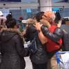 Des gens se serrent dans leurs bras à l'aéroport.