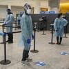 Des travailleurs portant masque, visière, gants et tenue de protection au centre de dépistage de l'aéroport Pearson.