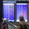 Un couple regarde le tableau des départs à l'aéroport de Zurich.