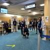 Neuf travailleurs posent devant le point de contrôle de l'aéroport de Vancouver.