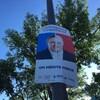 Une des affiches de la circonscription de Taschereau représentant un buste formé de la moitié de celui de François Legault et de la moitié de celui de Philippe Couillard, avec le slogan « Libécaquiste - Caquilibéral - On mérite mieux ».