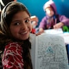 An Afghan girl shows her colouring book at a kindergarten in Mazar-e-Sharif in 2012.