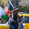 Un homme porte des drapeaux des talibans et de l'Afghanistan de différentes tailles.