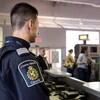 Un agent frontalier du Canada observe les passagers à une porte d'embarquement dans un aéroport