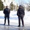 Deux policiers devant une grande résidence au sud d'Ottawa.