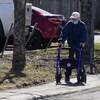 Un homme âgé marche avec un déambulateur sur un trottoir. Il porte un couvre-visage.