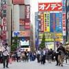 Une photo prise dans une rue du quartier Akihabara à Tokyo au Japon. On y voit des dizaines de personnes en train de marcher, dont plusieurs regardent leur téléphone. En arrière-plan et sur les côtés, on voit d'énormes panneaux colorés annonçant la présence de magasins.