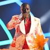 L'homme habillé d'un costume blanc et orange tient un micro et chante.