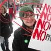Rachel Notley apparaît en arrière-plan de la photo d'une manifestante portant une pancarte opposée aux pipelines, aux sables bitumineux et aux pétroliers.