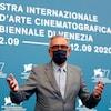 Alberto Barbera, masqué, devant le panneau officiel de la Mostra.