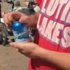 Un homme ouvre une cannette de bière à la plage.