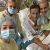 Un homme prend la pose à partir d'un lit d'hôpital avec son épouse et ses deux enfants.