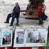 Deux hommes assis sur un banc public devant des affiches de candidats.