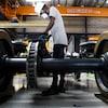 Un homme travaille sur du matériel roulant dans une usine.