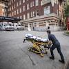 Un ambulancier pousse une civière devant un hôpital à Vancouver.
