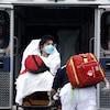 Des ambulanciers poussent dans une ambulance la civière d'une femme portant un masque sur le visage.