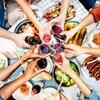 Une table garnie de plats avec des gens trinquant.