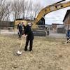 Trois personnes font la première pelletée de terre.