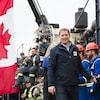 Andrew Scheer marche, souriant, près d'une rangée de travailleurs.