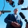Andrew Scheer est entouré de journalistes qui tendent des micros vers lui.