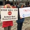 Trois manifestants tiennent des pancartes sur lesquelles on peut lire : arrêter le projet de loi 156, dire la vérité ne devrait pas être un crime et ne cachez pas la vérité.
