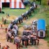 Plan en plongée d'une maquette de cirque où l'on voit des éléphants faire une longue file.