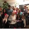 Une famille prend la pose devant un sapin de Noël.