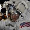 Dans sa combinaison d'astronaute, Anne McClain sourit à la caméra, avec la Terre en arrière-plan.